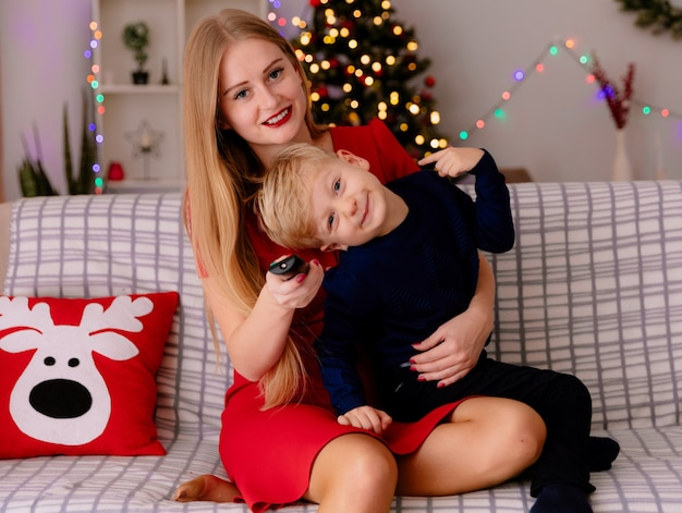 Felice madre in abito rosso con il suo bambino seduto su un divano che si diverte a guardare la tv insieme in una stanza decorata con albero di natale nel muro