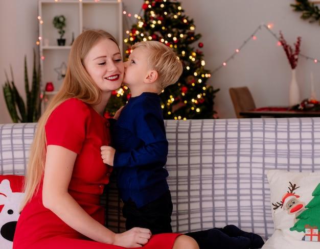 Felice madre in abito rosso con il suo piccolo bambino seduto su un divano piccolo bambino che bacia la sua allegra madre in una stanza decorata con albero di natale in background