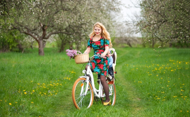 Happy mother riding city bicycle with baby in bicycle chair, in the basket lay a bouquet of lilacs