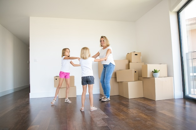Happy mother round dancing with two girls among unpacked boxes