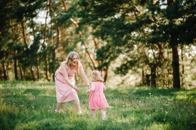 Счастливая мать бежит и ловит дочь на природе на летних каникулах. мама и девочка играют в парке во время заката. понятие дружной семьи. закройте вверх.