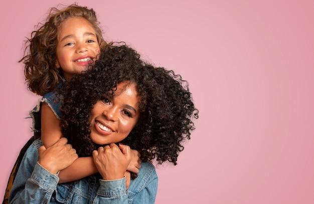 母の日おめでとう!かわいい小さな娘と愛らしい甘い若いアフリカ系アメリカ人の母親。