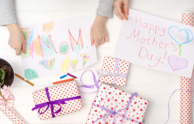 Happy mother's day card made by little child. girl's hands holding a handmade cards with giftboxes.
