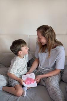 母の日おめでとう。子供の男の子はお母さんを祝福し、花にチューリップとポストカードを渡します。母と息子は笑顔で抱きしめます。家族の休日と一体感。母の日の挨拶のコンセプト。