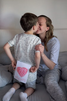 Happy mother's day. child boy congratulates mom and gives her flowers tulips and postcard. mum and son smiling and hugging. family holiday and togetherness. mother's day greeting concept.