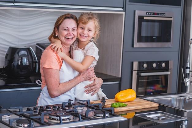 С днем матери! дочь ребенка и мама готовят и веселятся на кухне дома. семейный отдых и единение.
