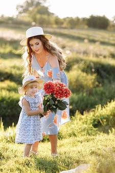 С днем матери. дочка ребенка поздравляет маму и дарит ей букет цветов на открытом воздухе.