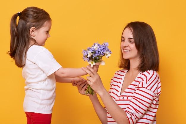 母の日おめでとう!子供娘はお母さんを祝福し、花束を差し出します。