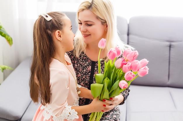 С днем матери. дочка ребенка поздравляет маму и дарит ей цветы тюльпаны. мама и девочка улыбаются и обнимаются. семейный отдых и единение.