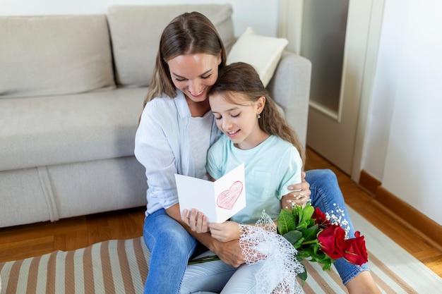 母の日おめでとう!子娘はお母さんを祝福し、はがきと花を贈ります。ママと女の子の笑顔と抱擁。家族の休日と一体感。