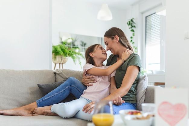 С днем матери! дочка ребенка поздравляет маму и дает ей открытку. мама и девочка улыбаются и обнимаются. семейный отдых и единение.
