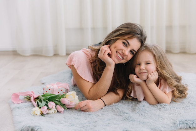 Happy mother's day. child daughter congratulates mom and gives her flowers tulips and gift