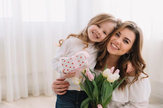 С днем матери. дочь ребенка поздравляет мам и дарит ей цветы тюльпанов и подарок.