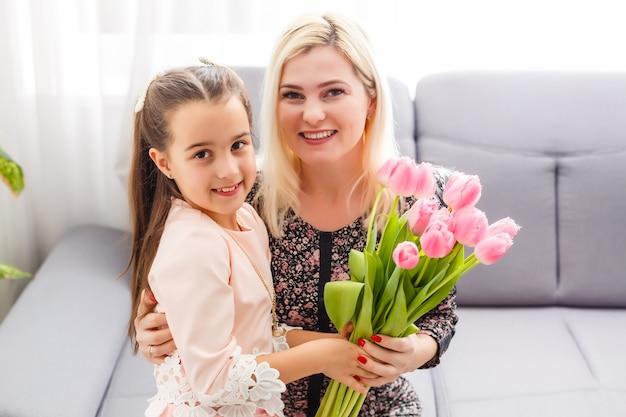 母の日おめでとう。子娘はお母さんを祝福し、花にチューリップを贈ります