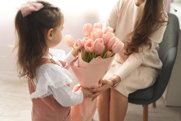 해피 어머니의 날! 어린 딸은 엄마를 축하하고 분홍색 꽃 튤립을 줍니다.