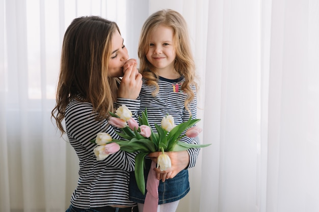Happy mother's day. child daughter congratulates moms and gives her flowers tulips.