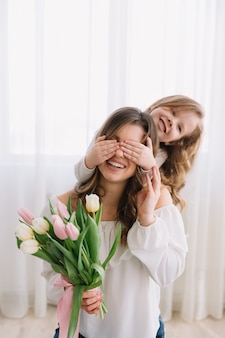 Happy mother's day concept. child daughter congratulates mom and gives her flowers tulips