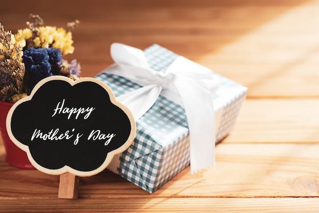 幸せな母の日のコンセプト。ギフトボックス花、木製の木製のタグ木製のテーブル。
