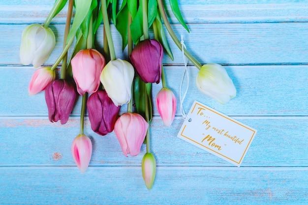 木製のテーブルの上に花と紙のタグで幸せな母の日コンセプト