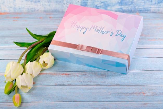 ギフト用の箱と木製のテーブルの上に花の幸せな母の日コンセプト