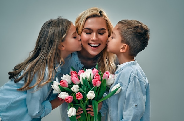 Happy mother's day! cute charming girl and boy give their beautiful mother a bouquet of tulip flowers and kiss on the cheeks isolated on a gray wall.