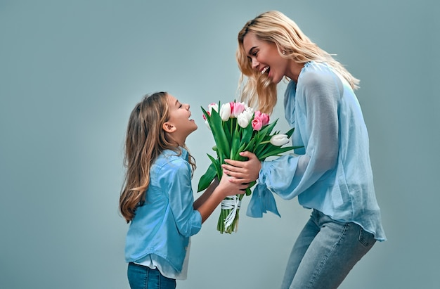Happy mother's day! cute charming girl gives her beautiful mother a bouquet of tulip flowers isolated on gray wall.
