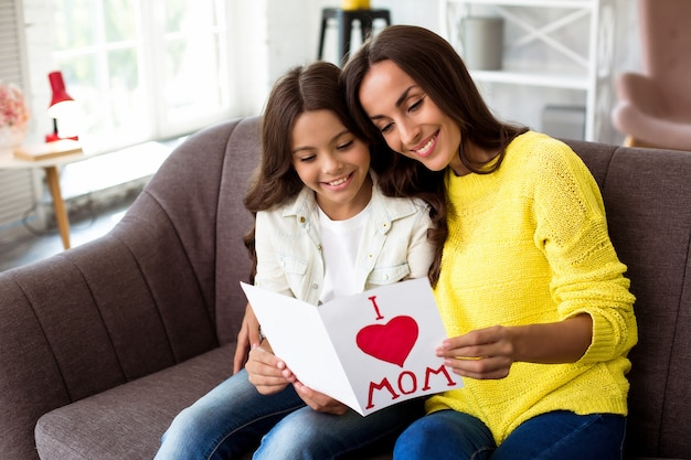 С днем матери. милая дочка поздравляет маму и дарит ей открытку. мама и девочка улыбаются и обнимаются на диване. семейный отдых и единение