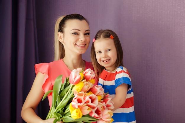 母の日おめでとう!娘はお母さんを祝福し、チューリップに花の花束を与えます。幸せな子供と親、家族。