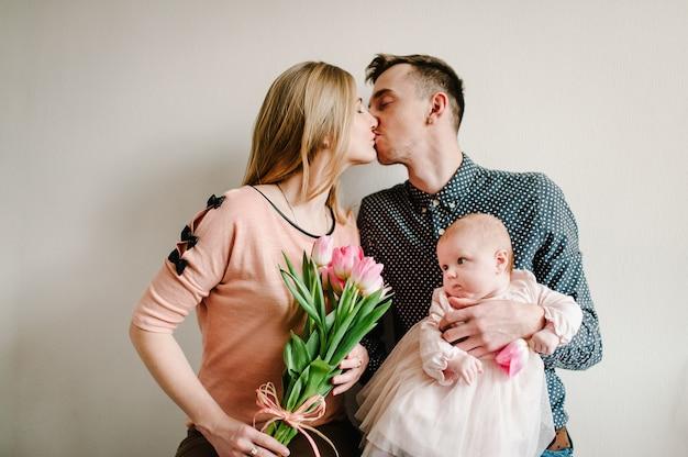 母の日おめでとう!お父さんと娘はお母さんを祝福し、彼女の花束にチューリップを与えます。母の日のコンセプト