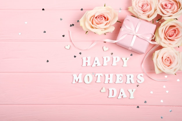 Happy mother's day decorations, bouquet and gifts on pink background