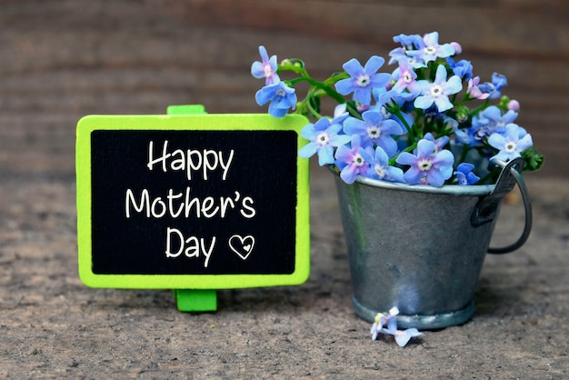 Happy mother's day.forget-me-not flowers in small metal bucket on old wooden table.selective focus.