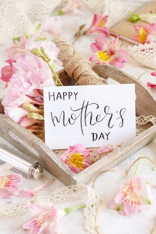 ピンクの花の間の木製トレイに幸せな母の日の手書きカードがクローズアップ