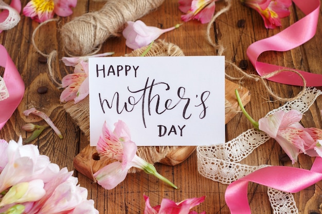 Happy mother's day handwritten card on a wooden table between pink flowers close up
