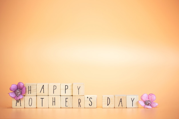 紫色の春の花と木製の立方体の幸せな母の日の碑文