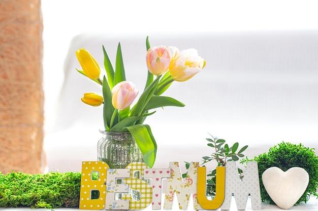 母の日おめでとう。白い背景の上の手紙。春のチューリップの新鮮な美しい花束のあるリビングルームの木製テーブルに母の日のための木製の碑文。