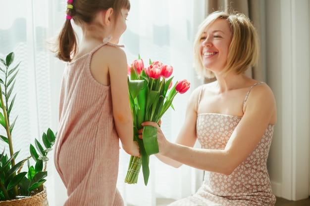 С днем матери! маленькая девочка поздравляет ее мать и дарит ей цветы. счастливая мама и дочь проводят время вместе. сосредоточьтесь на тюльпанах.