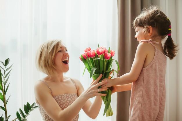 С днем матери! маленькая девочка поздравляет ее мать и дарит ей цветы. мама и дочь проводят время вместе. сосредоточьтесь на тюльпанах.