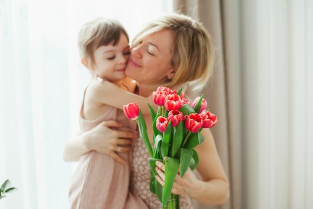 С днем матери! маленькая девочка обнимает ее мать. женщина, держащая цветы. мама и дочь улыбаются и проводят время вместе. сосредоточьтесь на тюльпанах.