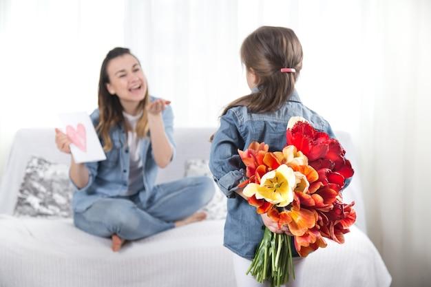 С днем матери. маленькая милая дочка с большим букетом тюльпанов поздравляет маму. в интерьере гостиной концепция счастливой семейной жизни