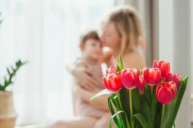 С днем матери! мама и дочь обнимаются и проводят время вместе. сосредоточьтесь на тюльпанах.