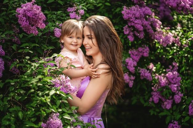 母の日おめでとう!ママと女の子の笑顔とハグ。
