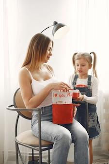 С днем матери или днем рождения. милая мать распаковывает подарочную коробку. подарок от маленькой дочери.