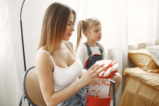 幸せな母の日または誕生日。かわいいお母さんがギフトボックスを開梱します。幼い娘からプレゼント。