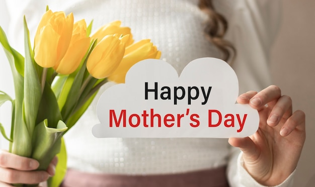 Happy mother's day. promotional content for mother's day. card with the inscription and flowers in hands.
