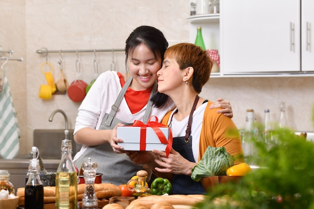 Happy mother's day! teenager daughter congratulates mother and gives a gift in kitchen at home