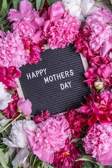 Счастливый день матери текст и пион. стильная цветочная открытка. рукописные надписи. день матери