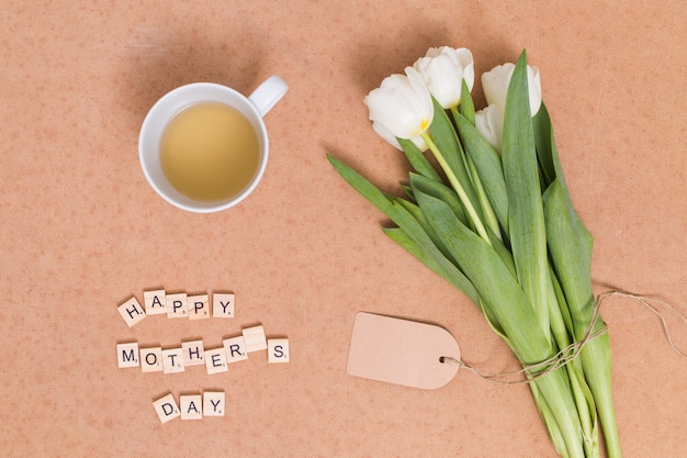 Happy mother's day text; lemon tea with white tulip flowers on brown backdrop