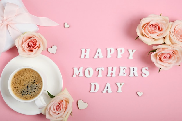 Happy mother's day text with cup of coffee, roses and gift on pink background