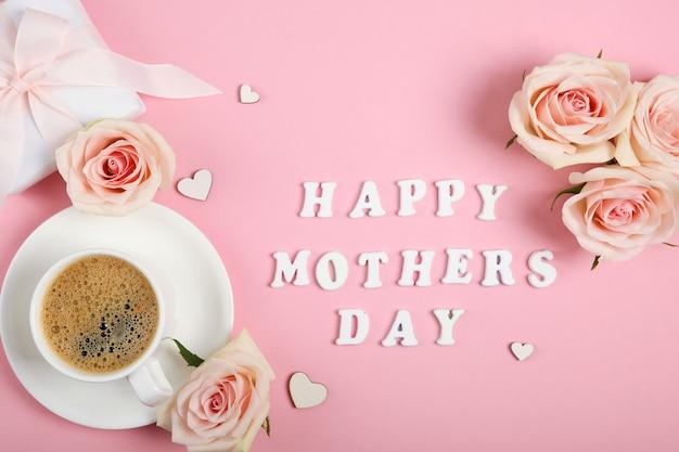 ピンクの背景に一杯のコーヒー、バラ、ギフトと幸せな母の日のテキスト