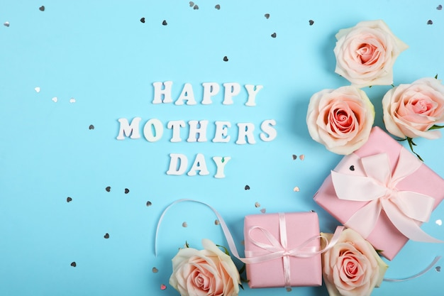 Happy mother's day text with roses and gifts on blue background